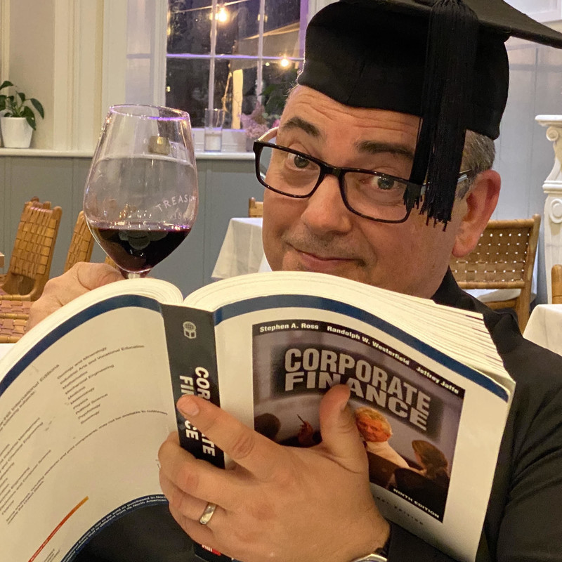 A photograph of a man wearing a black graduation cap with a tassel and black framed glasses. He is holding a wine glass and a corporate finance textbook.
