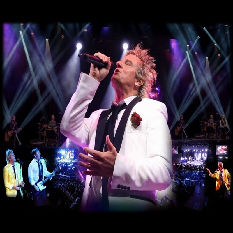 A photo of a man wearing a white suit singing into a microphone. The background features a photo of a stage and other people playing musical instruments.