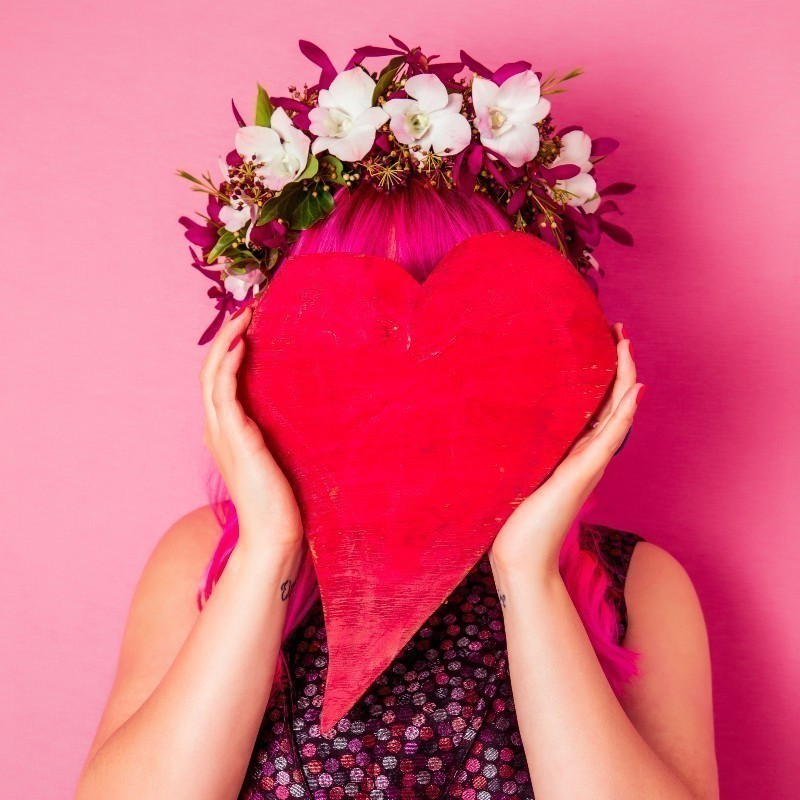 A person holds a love heart shape in front of their face. They have pink hair and are wearing a flower headband.