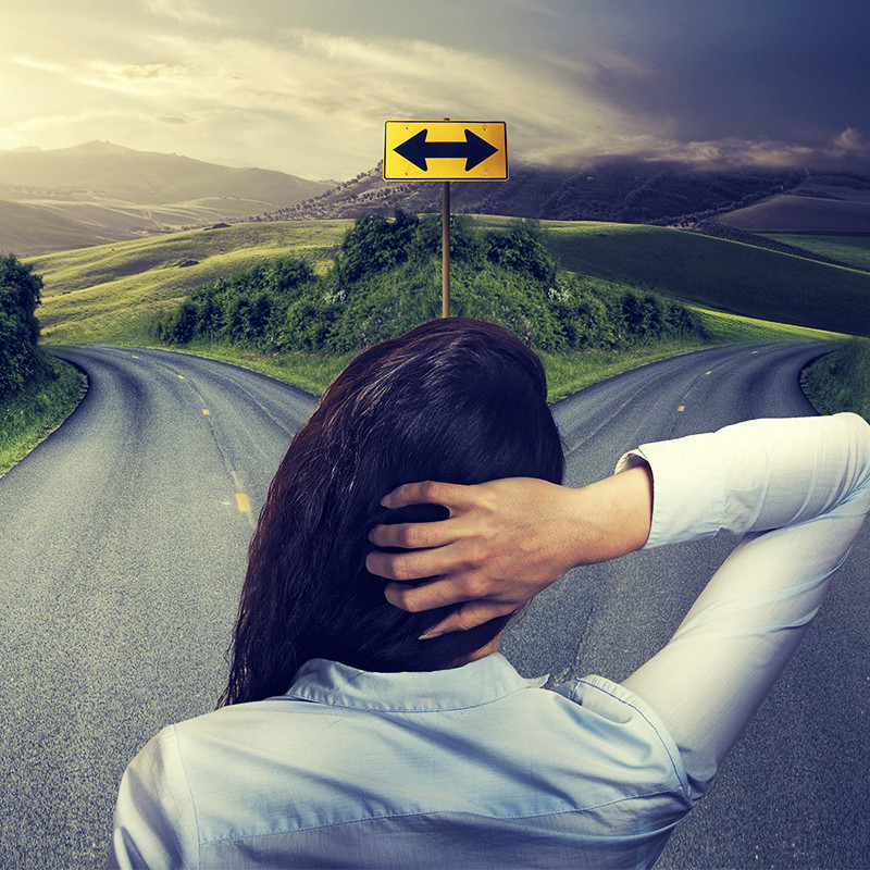 At the Crossroads - A person standing with their back to the camera. They have long dark hair, one hand on the back of their head. In front of them there is a forked road with a yellow street sign featuring a double ended arrow. There is grass, mountains and clouds in the distance.