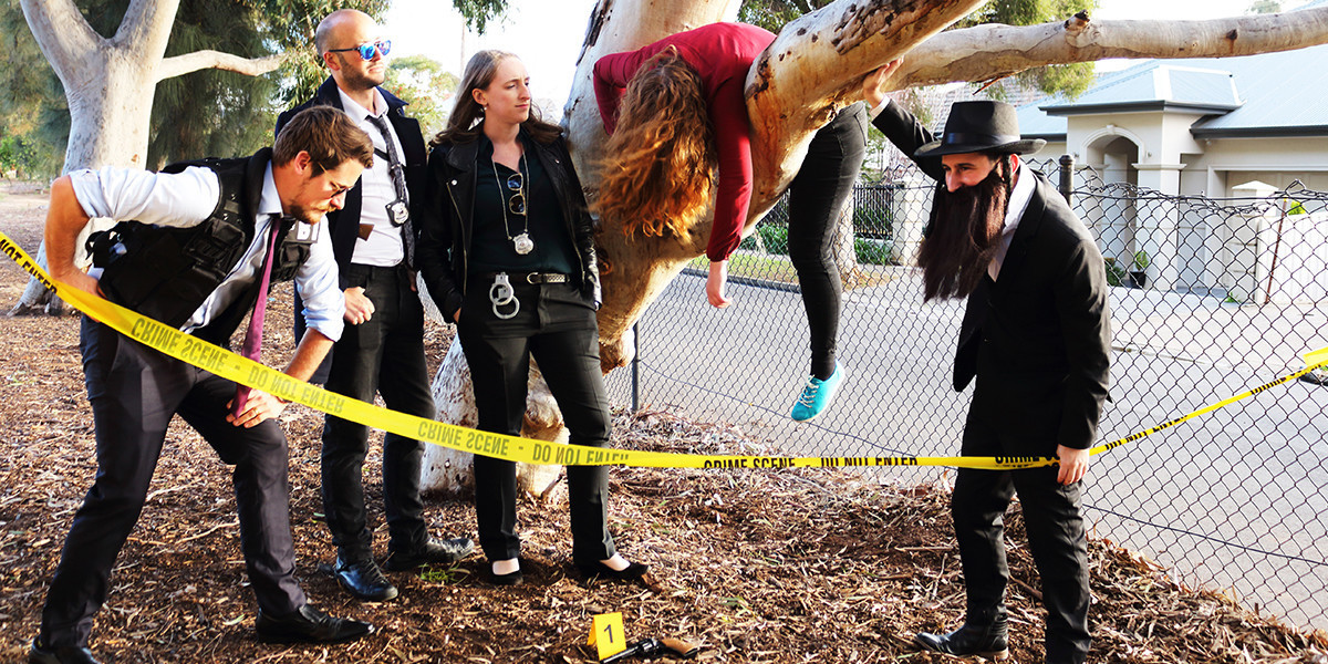 A photo of four people dressed as detectives standing around a tree where a person wearing a red top is hanging off, pretending to be dead. There is a crime scene tape around them.