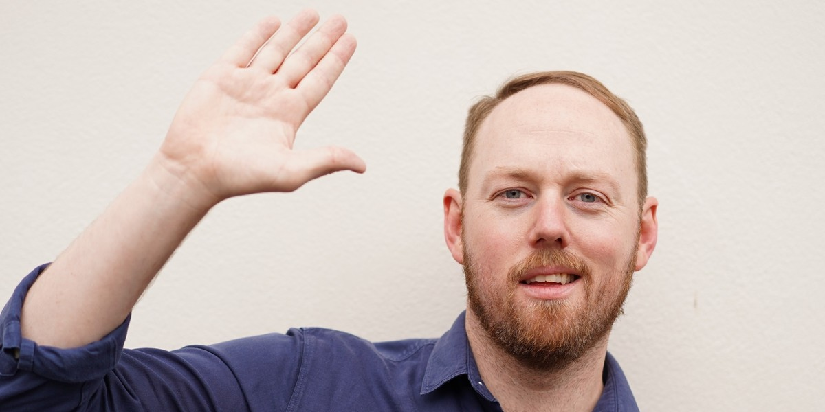 A photograph of a man with short strawberry blonde hair and beard smirking at the camera with one hand in the air, as if to wave. The background is a cream colour.