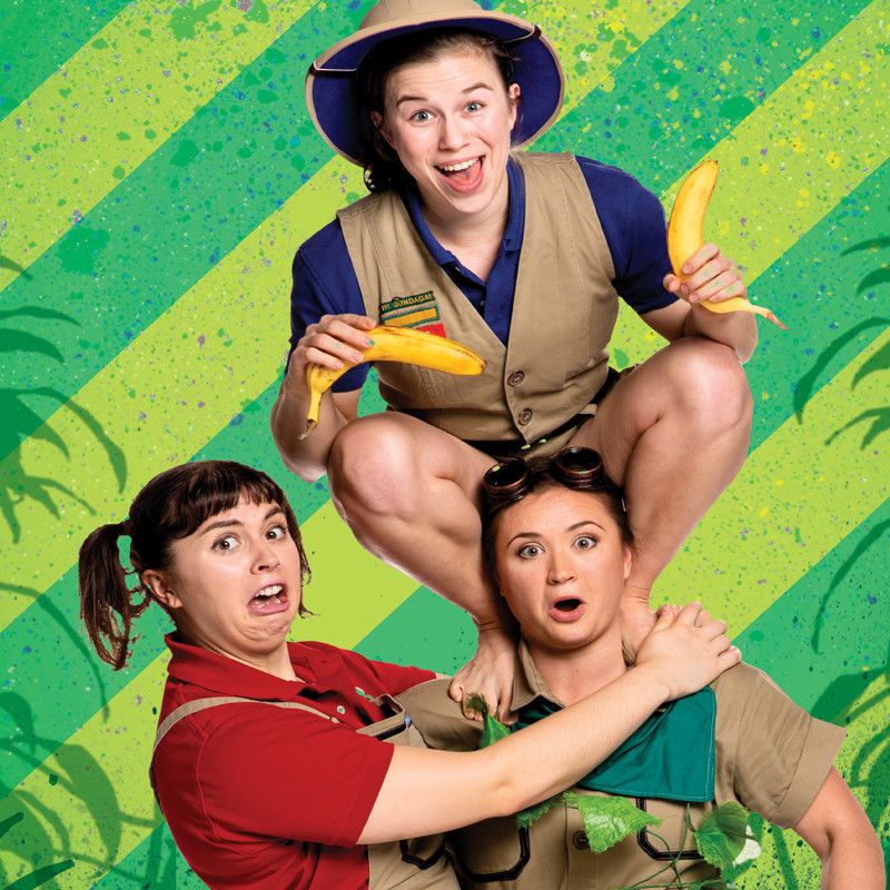 Three people are posed in front of a diagonally striped dark green and light green background with palm fronds. One person holding two bananas squats on the shoulders of another surprised looking person. To the left another person with pigtails pulls a funny face. They are all wearing khaki coloured outfits in the style of Safari suits.