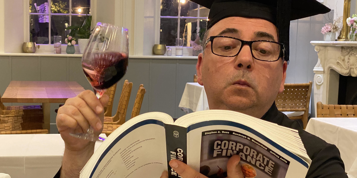 A photograph of a man wearing a black graduation cap with a tassel and black framed glasses. He is holding a wine glass and a corporate finance textbook which he is peering at.
