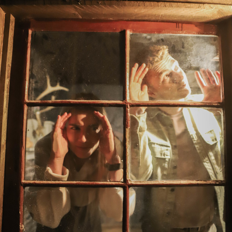 A photo of two people peering through a window.
