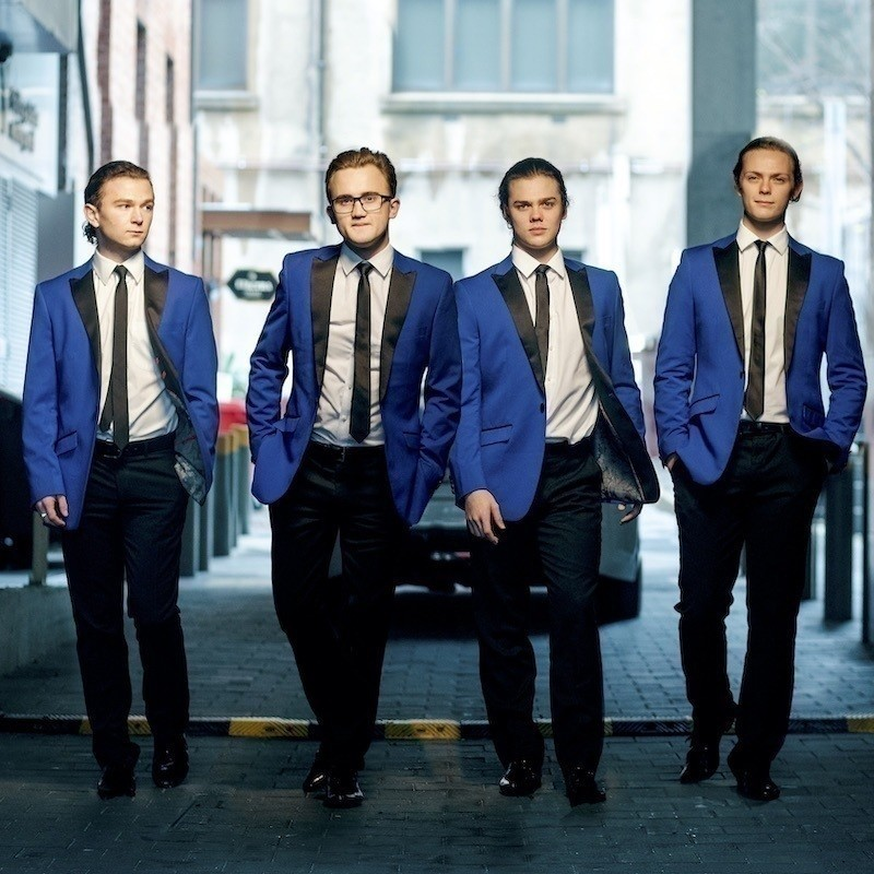A photo of four men walking with blank expressions on their faces. They are wearing matching blue suit jackets, black pants, black ties and white shirts.