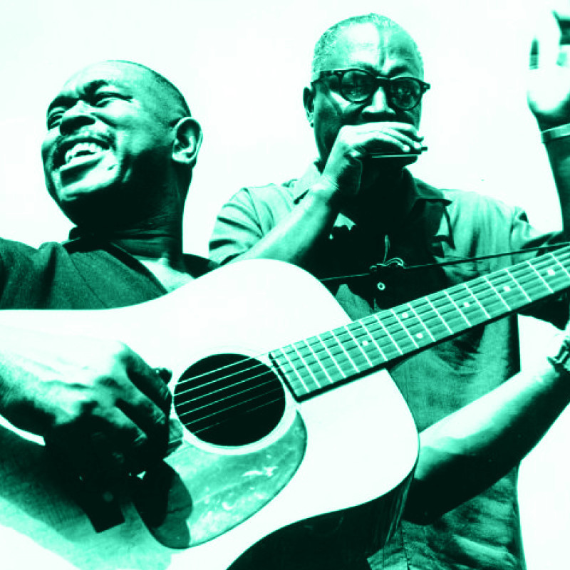 A History of Mississippi Blues - An image of two men playing musical instruments. The man on the left is playing guitar and smiling to the side. The man on the right is holding a harmonica to his house and is wearing black framed glasses. The image has a green filter on it and the entire image is shades of green, black and white.