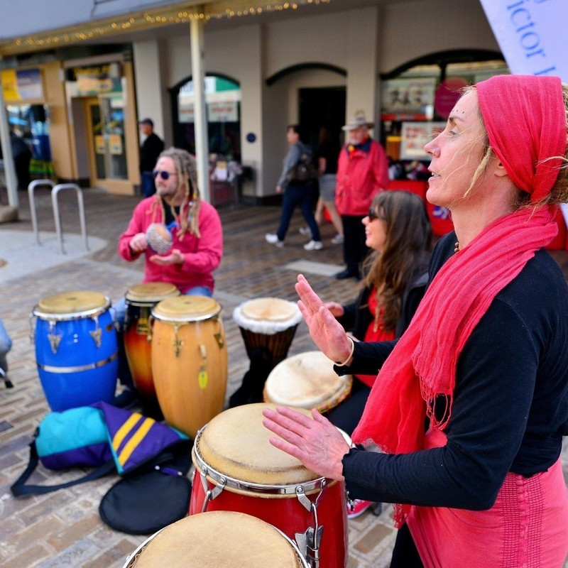 Fringe at Victor Harbor - Three people in a semi-circle play a variety of different sized drums with their hands. They are standing on a street outside some retail shops with people in the background.
