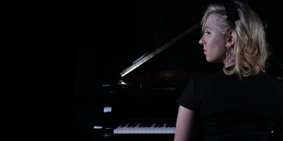 A photograph of a woman seated at a piano taken from behind. She has her head turned to the left of the image. She is wearing a black t-shirt and has a black hairclip in her hair. Her hair is blonde and sits at her shoulders.