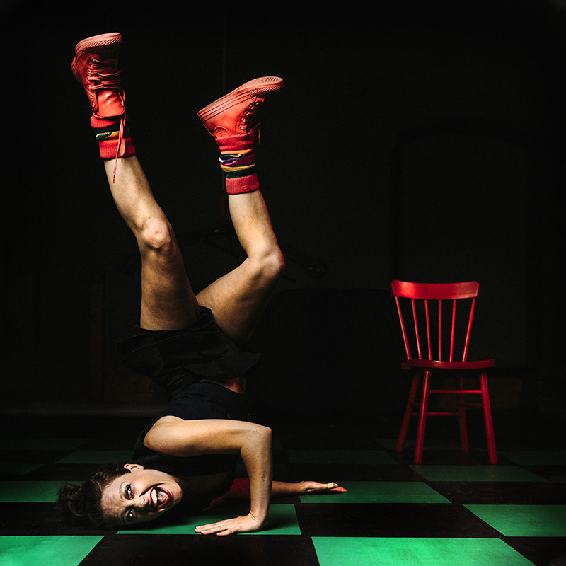 A photo of a person performing a handstand with their face resting on the ground. They have a animated expression on their face. They are wearing a black t-shirt and black shorts with bright red sneakers and socks. Next to them is a red chair. The ground features a green and black checkered design.