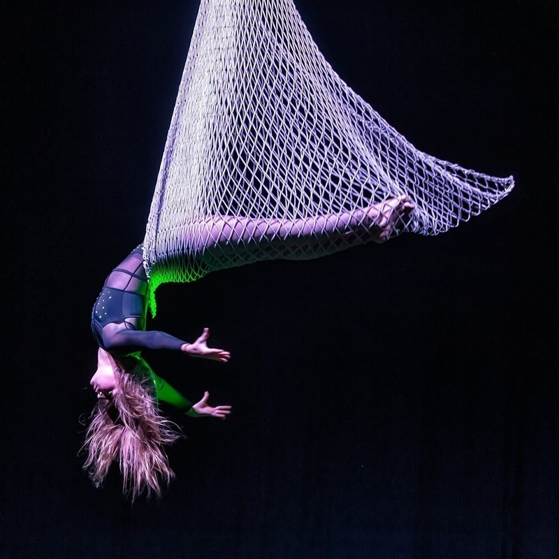 Aerialicious - A triangular shaped white net is suspended with a performer lying in it. The top half of their body is bending backwards out of the net. They are wearing a black skin tight costume, their hands are extended above their head towards the ground, they have long blond hair hanging down. The background is dark with a green light highlighting the back of the performer.