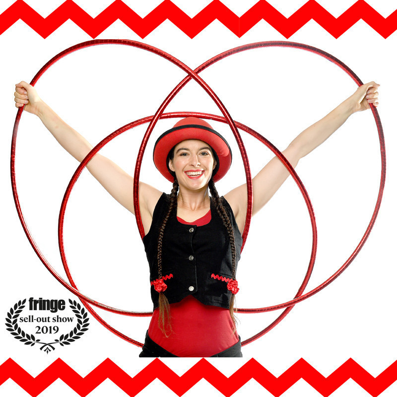 A photo of a woman holding her arms out holding three red hula hoops over and around her head. She is wearing a red hat, red singlet and a black vest. The background is white with a red zig-zagging line and the top and bottom of the image. A logo in the bottom left corner reads 'Fringe Sell-Out Show 2019'.