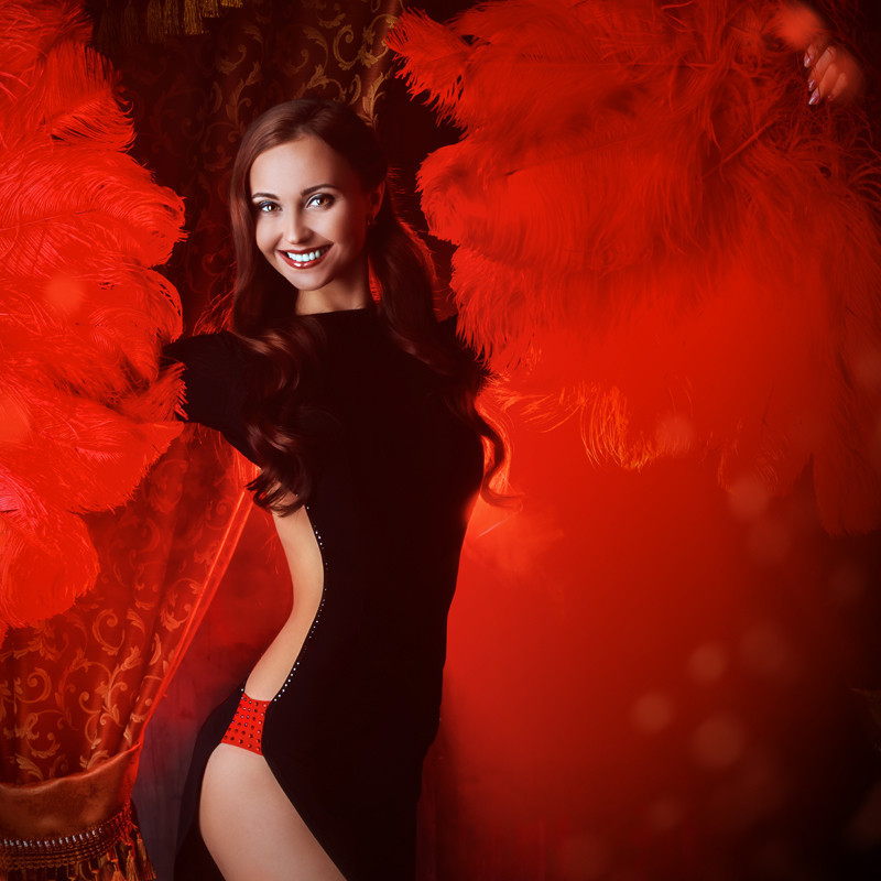 Choo and Peek - A photograph of a woman with long brown hair smiling. She is wearing a long brown dress that is exposed on the side. The background of the image is red and she is holding two large red feathered hand fans.