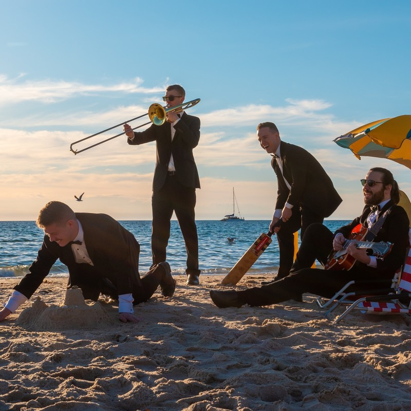 A photo of four men on the beach. They are all wearing black suits, white shirts and black bow ties. On the left of the image there is a man building a sandcastle. In the middle of the image there are two men standing up, one is playing the trombone and the other is holding a cricket bat. On the right of the image there is a man sitting down playing guitar. In the background there is the ocean and a ship sailing on the water in the distance.