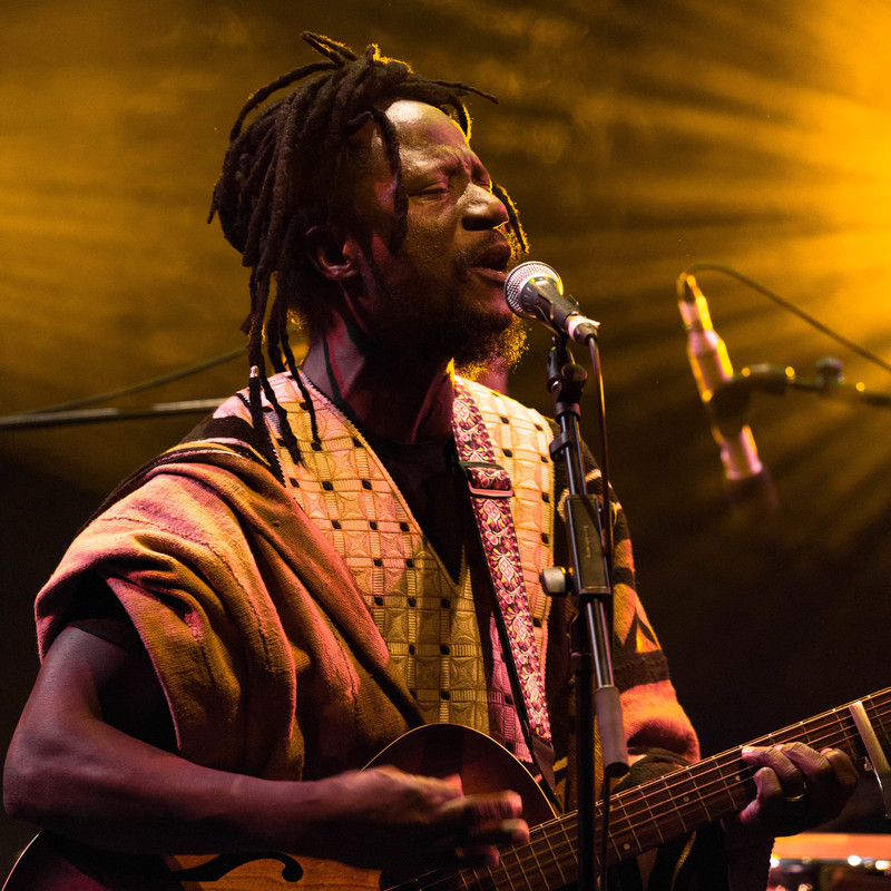 A man with dark skin and long dreadlocks tied up on the top of his head sings into a microphone on a stand while playing the guitar. He wears a cream coloured, patterned flowy jacket, the lighting behind him is glowing yellow.