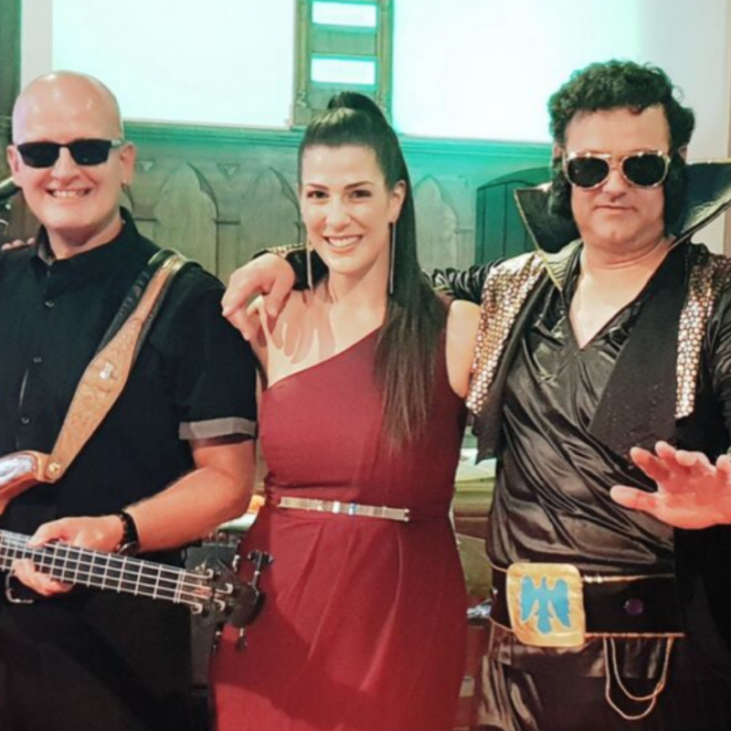 A photo of three people smiling. The person on the left of the image is wearing a black shirt and black glasses and is holding a guitar in front of his body. The person in the middle is wearing a red dress and the person on the right of the image is wearing a black costume with a large collar with gold framed glasses.