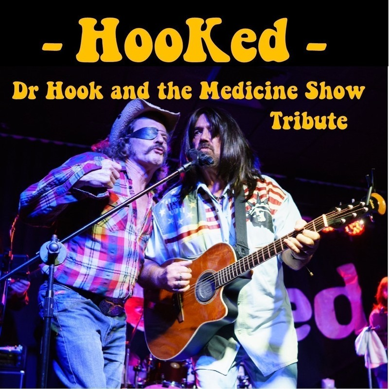 A photo of two men singing into a microphone. The man on the left is wearing an eye patch, red checked shirt and jeans. The man on the right has long black hair and is holding a guitar. The text reads 'Hooked' and 'Dr Hook and the Medicine Show Tribute' in yellow font.