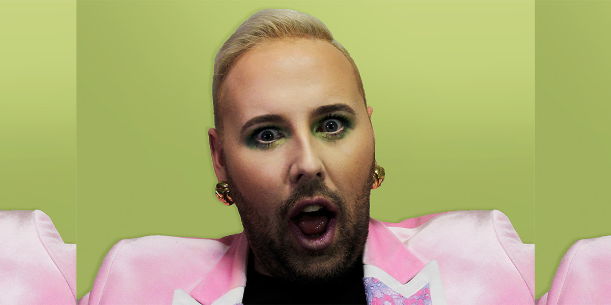 Queer artist Faz wears a pink sating jacket, heavy green eye makeup, large earrings and appears shocked before the camera