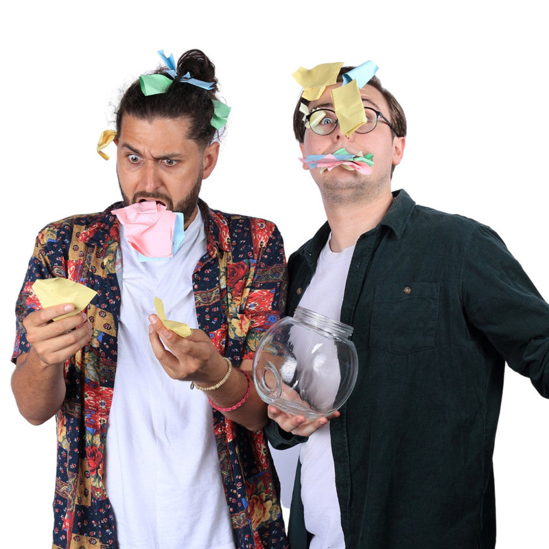 A photo of two men with colourful sticky notes stuck in their hair and mouth with animated facial expressions.