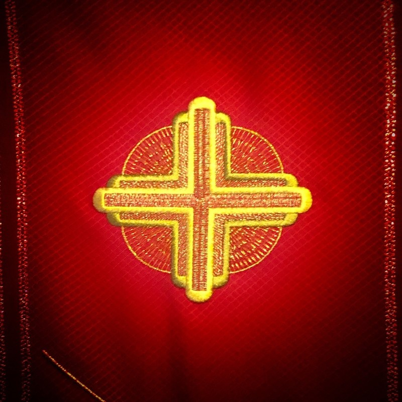 An image of a detailed yellow embroidered cross on a red background.