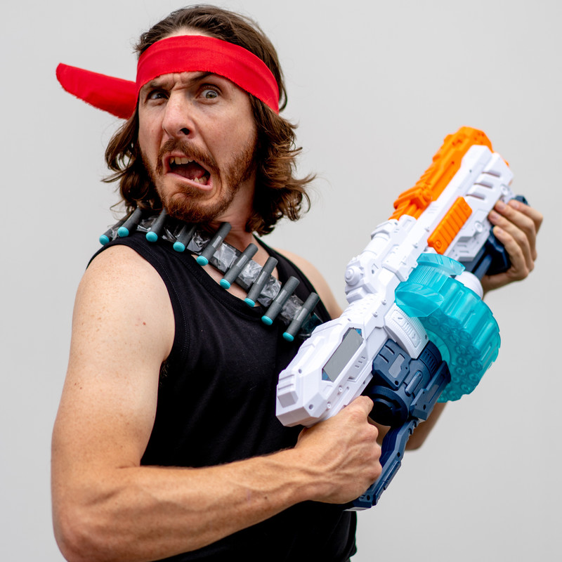 A photo of a person with a bewildered expression on their face. They are wearing a black singlet and a red bandana across their forehead. They are holding a large plastic gun in front of their body.