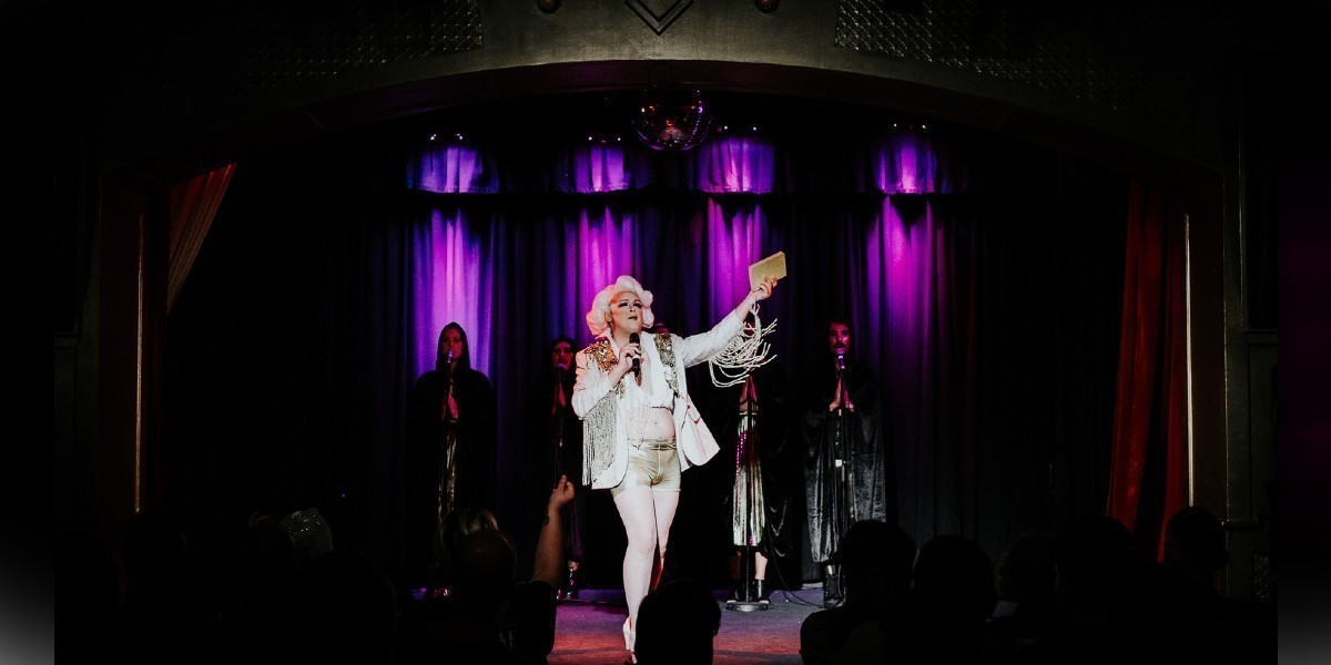 A photograph featuring a person in the middle of the stage wearing a white hat and a white jacket and pants which have gold embellishments. They are holding a microphone in front of their chest and gesturing to the side with the other hand, holding a piece of paper. Behind this person, are four backup performers standing up behind microphone stands. The curtain behind the backup performers is illuminated with purple light.