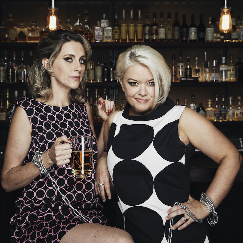 Two women are in front of a bar with liquor lined shelves. The woman on the left has long dark blonde hair, she is sitting on a bar stool, she wears a pink and black patterned dress and is holding a pint of beer. The woman on the right has short blonde hair in a bob, she has one hand on her hip and her elbow on the bar, she wears a black and white patterned dress. Both women are holding the ends of a chain. They are both looking at the camera, the blond woman has a cheeky smile.