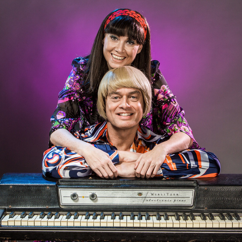 A photo of two people smiling. They are leaning on a keyboard and are both wearing multi-coloured long-sleeved shirts. The person at the front of the image has a blonde bowl cut and the person standing behind them has a red headband on.