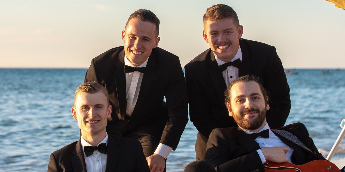 A photo of four men smiling. They are wearing black suits, white shirts and black bow ties.