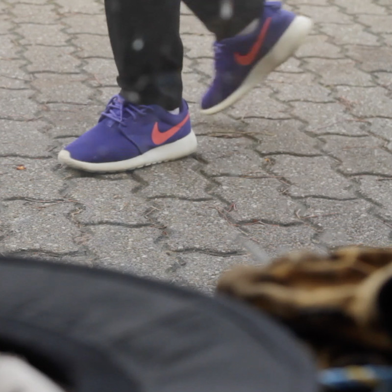 7 Day Notice - A zoomed in photograph of a person's feet. They are walking on a grey brick footpath and are wearing purple shoes that have an orange Nike swoosh logo on them.