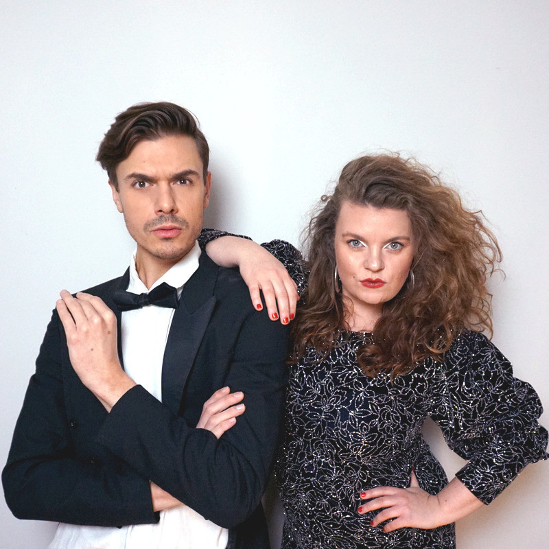 A photo of a man and a woman with serious facial expressions. The man is wearing a black suit jacket, white shirt and black bow tie. The woman is wearing a black dress with silver embellishments and is resting her arm on the mans shoulder.