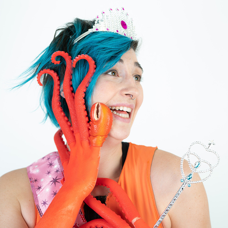 A photo of a person with blue hair and orange tentacle like fingers placed on the side of their face. They are also wearing a silver tiara and holding a silver wand.