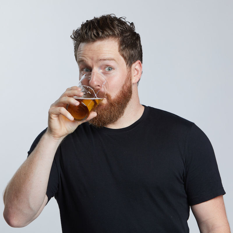 Nick Cody - Dad Bod - A photo of a guy wearing a black t-shirt drinking a beer. He has short hair and a full beard.