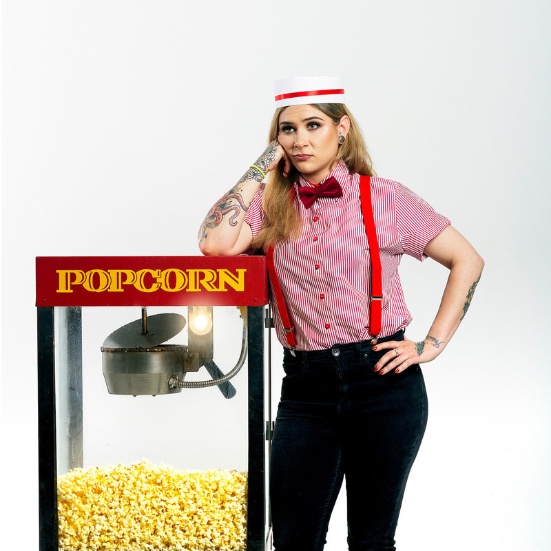 Bella Green is Charging For It - A photograph of a woman leaning on a popcorn machine staring into the distance. The woman is wearing a white hat, red and white shirt with a red bowtie and black pants with red suspenders. She also has tattoos that cover her forearms of various colours and shapes. The popcorn machine is filled with yellow popcorn, and has a red lid that features the writing that reads, 'popcorn' in a yellow font.