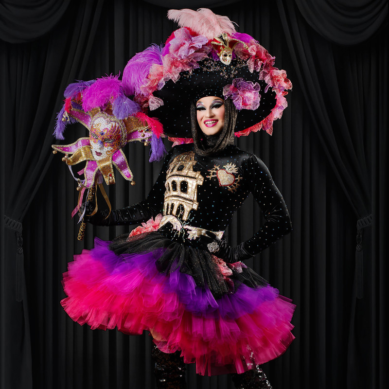 The Gaiety Garden - A photo of a person wearing a black outfit detailed with gold and silver. The skirt features multiple layers of pink and purple tulle. They are also wearing an extravagant large hat that has pink and purple flowers and feathers on it. In one hand they are holding a white mask that has been detailed with pink and gold glitter.