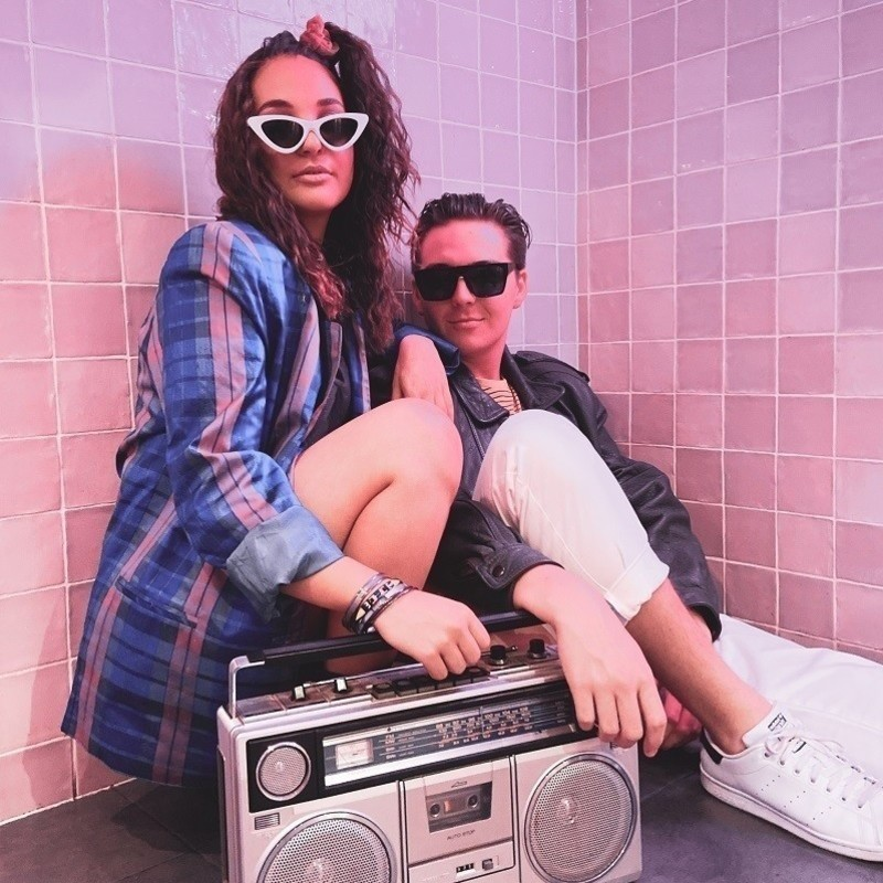 A girl and a boy with sunglasses crouching by a silver boom-box. The girl on the left is wearing a blue and pink blazer and white framed sunglasses. The boy is wearing a black jacket, white pants, and white sneakers with black framed sunglasses.