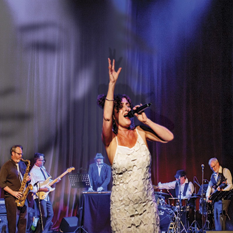 A photo of a woman performing on stage. She is passionately singing into a microphone and has one hand up in the air. She is wearing a white dress. The background features the band members playing a range of musical instruments.