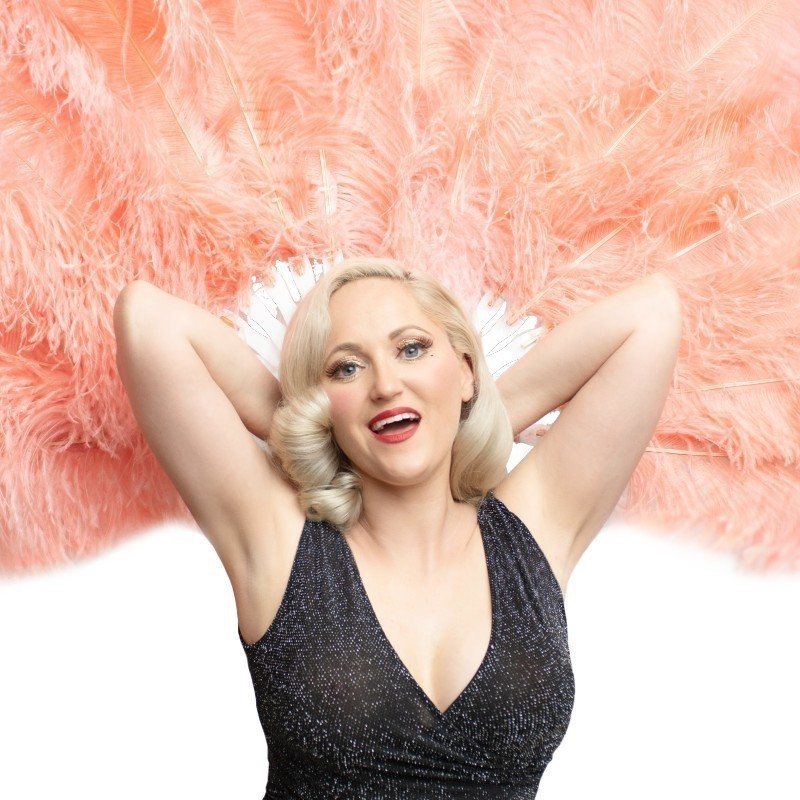 Fringe Fatale Student Showcase - A photo of a woman wearing a sparkly black sleeveless dress. She has a delighted smile on her face. Her arms are bent behind her head, and the background behind her is made up of large peach coloured feathers.