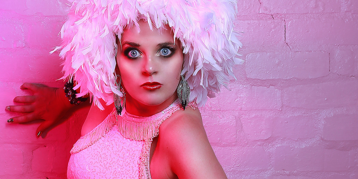 A photo of a person wearing a white feathered wig on their head, silver earrings and a white beaded dress. They have a serious look on their face. The background is pink.
