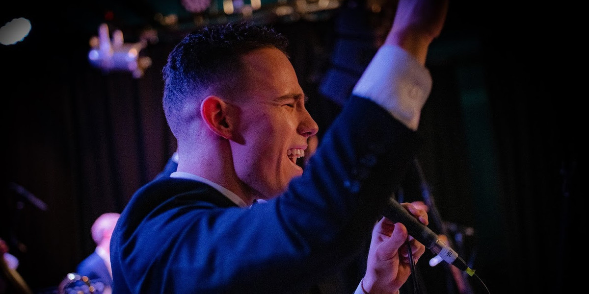 A photo of a man wearing a suit singing into a microphone.