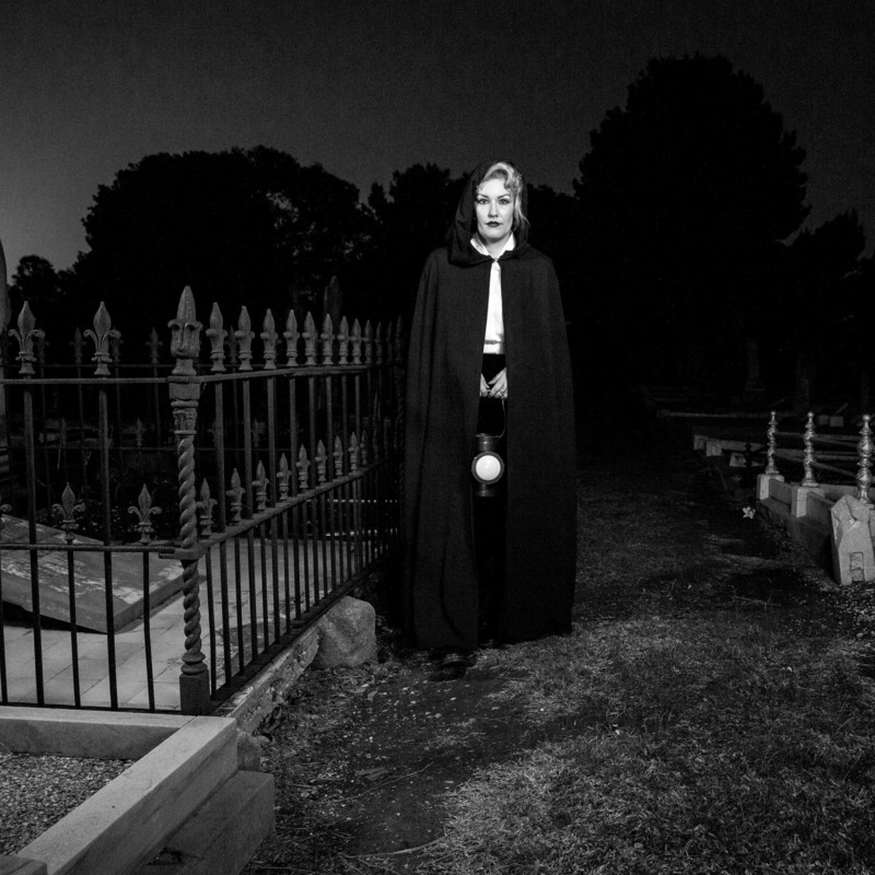A black and white photo of a person standing in a cemetery wearing a black cape holding a lantern.