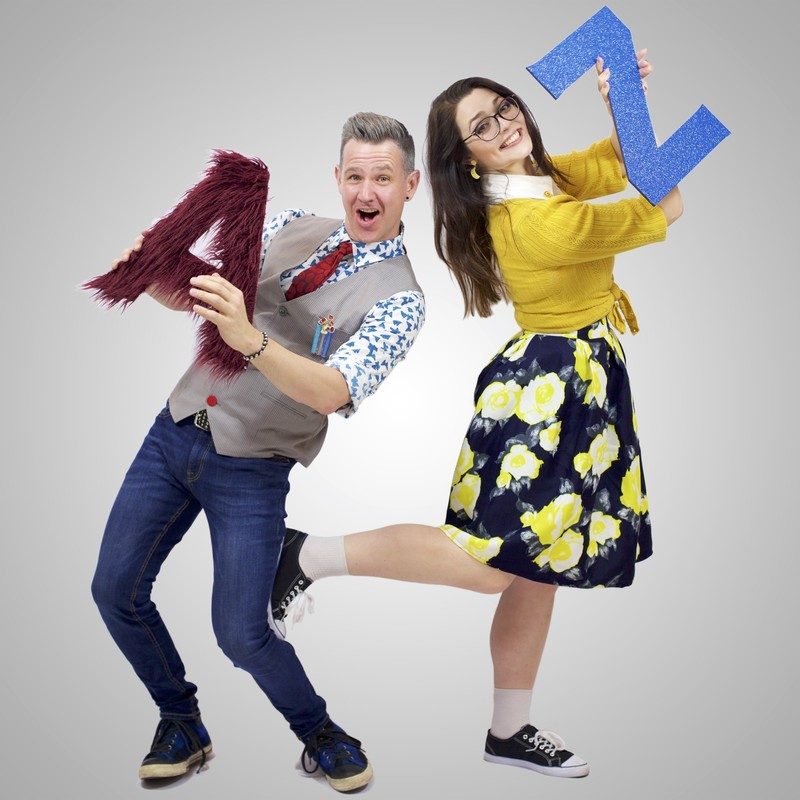 A photo of two people smiling. The person on the left is wearing a blue patterned shirt, grey vest and blue denim jeans while holding a letter 'A' which is red and fluffy. the person on the right is wearing a yellow cardigan, and a yellow floral skirt and is holding the letter 'Z' which is blue and glittery.