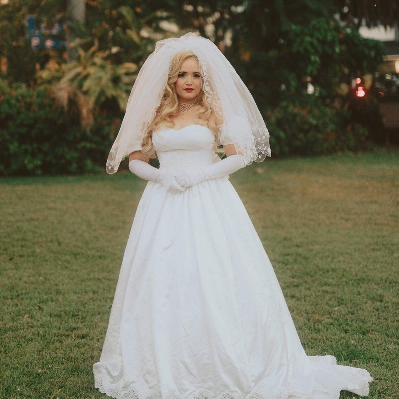 A photo of a woman standing in a white wedding dress. She has long blonde hair and is wearing white veil and white elbow length gloves.