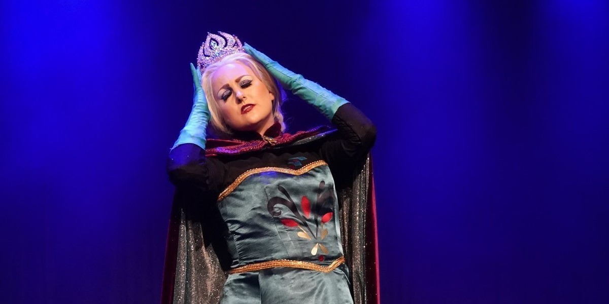 A photograph of a performer on stage. The performer is wearing a long-sleeved gown costume and a silver tiara on their head. Their hands are placed on the sides of their head.