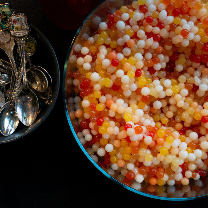 A small bowl of teaspoons on the left, a large bowl of multi-coloured salmon roe.
