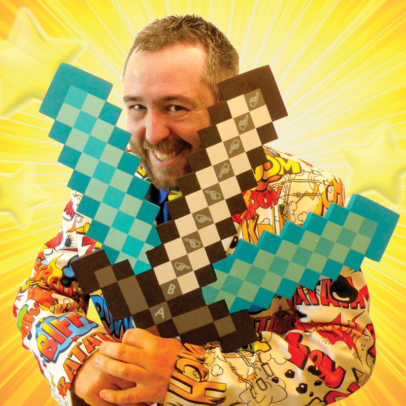 GAME ON 3 - A smiling man with short dark hair and a short beard wears a suit covered with comic book slogans. He holds a prop of a pixelated three pronged sword. The background is yellow with yellow stars.