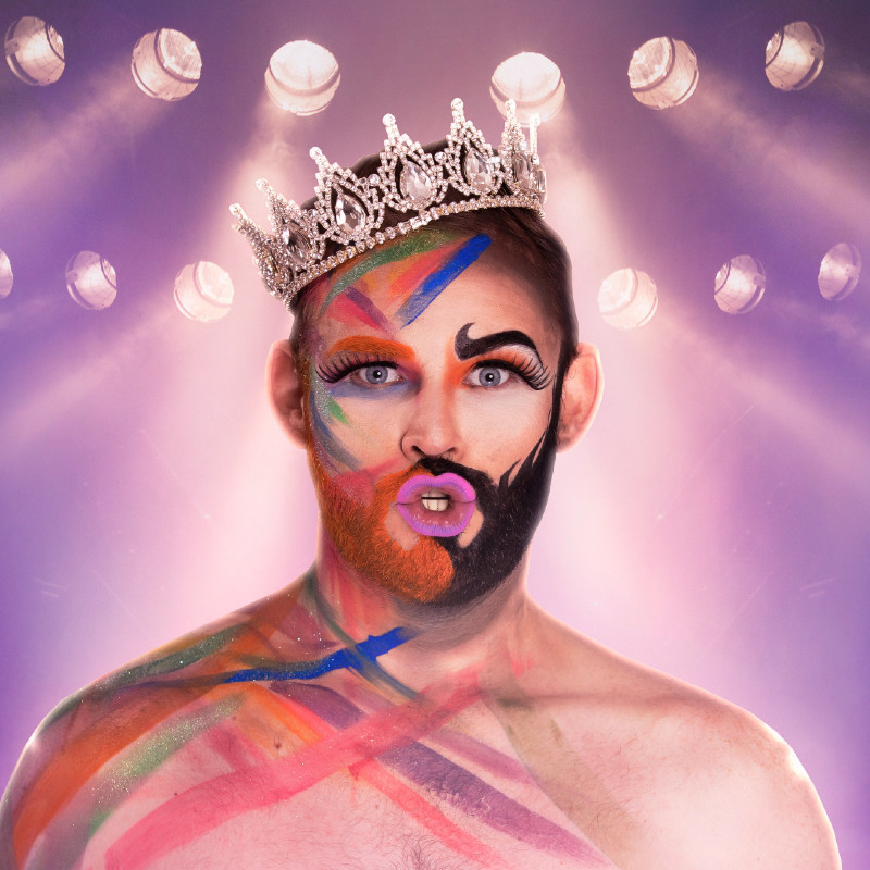 A topless performer is covered in multi-coloured stripes of paint, half of their beard is painted orange and the other half is painted black. They wear a plastic crystal crown on the side of their head. There are twelve large spotlights in the background giving a pale purple light.