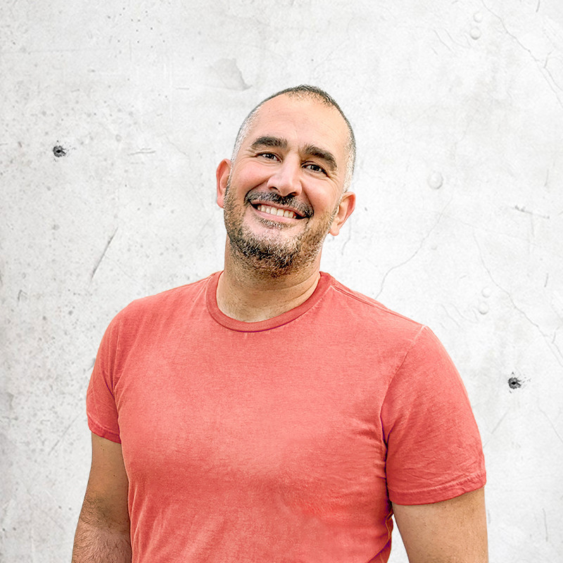 A photo of a man wearing a faded red t-shirt smiling.