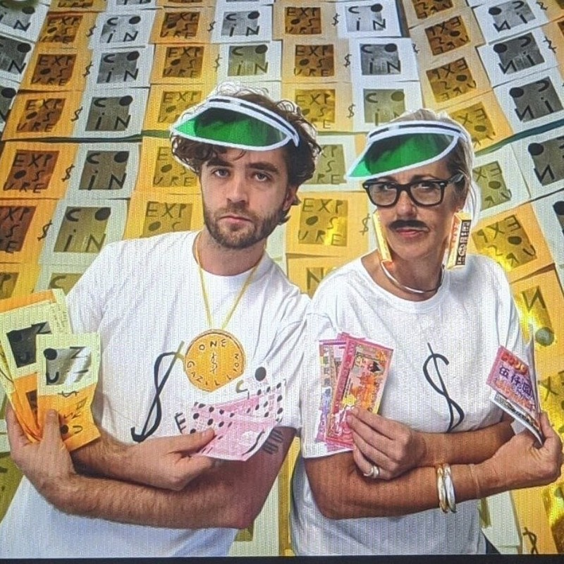 The New Money - A photo of two people posing with their arms crossed. They are wearing green visors, white t-shirts with dollar signs ($) and they are holding several small leaflets in both hands.