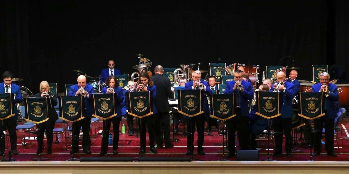 A photograph of a band performing on stage. There is a row of performers standing up in the front of the stage, each behind a music stand. They are all playing brass instruments and wearing blue suit jackets with black pants. Behind them sits the rest of the band.